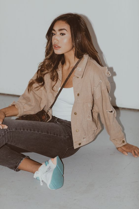 a casual outfit with a white tan top, black cropped jeans, a tan ripped denim jacket and white trainers