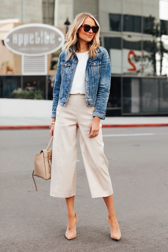 a casual outfit with a white top, tan culottes, a blue cropped denim jacket, nude shoes and a bag