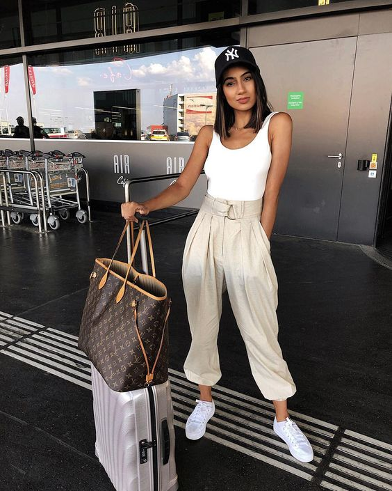 a casual summer outfit with a white tank top, neutral high waisted pants, white sneakers and a cap