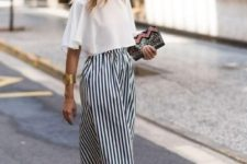 a chic and bold look with a white crop top, striped knee skirt, blush block heel mules and a printed clutch