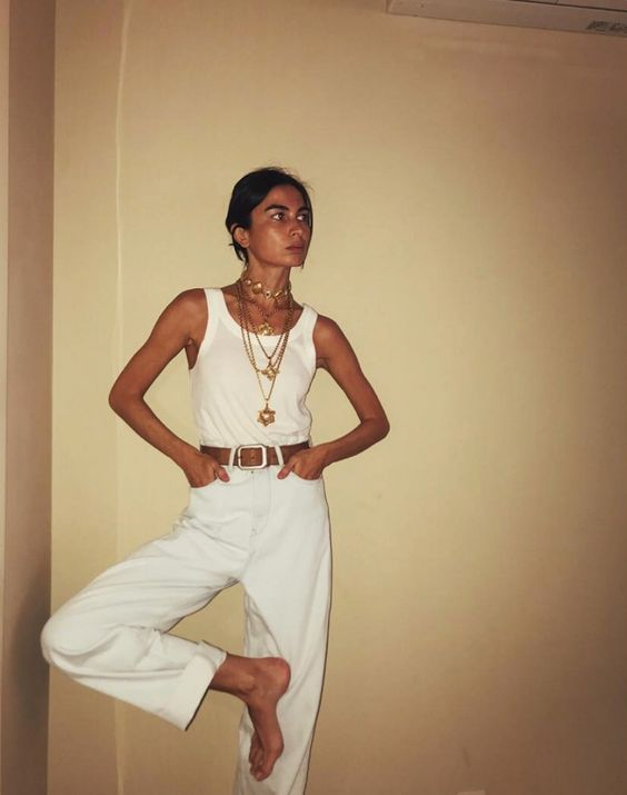 a chic summer look with a white tank top, wideleg high waisted pants, a belt and layered chunky necklaces