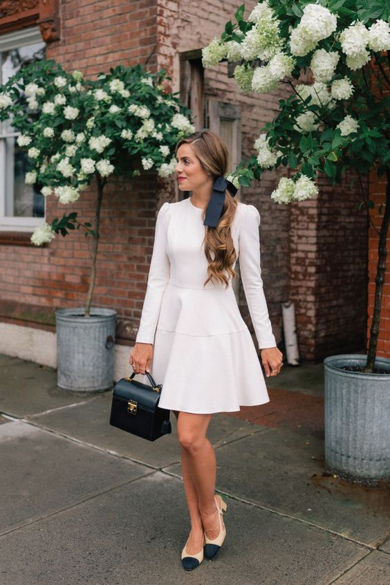 a chic work look with a white A-line over the knee dress, two tone slingbacks, a black ribbon and a black bag