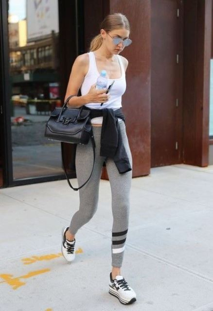 a daily look by Gigi Hadid - a white tank top, grey leggings, black and white trainers and a small bag