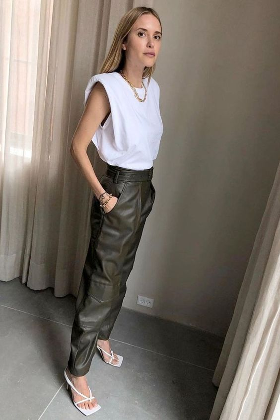 a fashionable look with a white padded shoulder tee, brown leather pants, white square toe heels