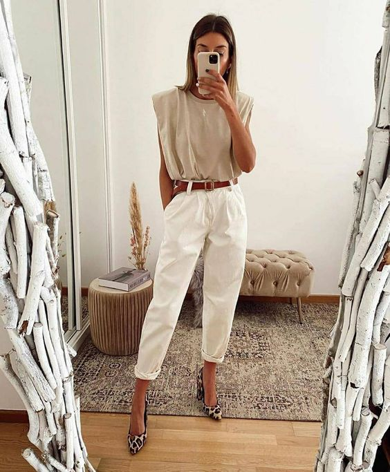 a fashionable summer outfit with a neutral padded shoulder tee, white pants, a brown belt and animal print shoes