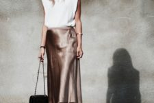 a glam look with a white padded shoulder tee, metallic satin midi skirt, shiny shoes and a black bag