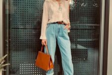 a glam look with blue baggy jeans, a neutral shirt, pearls, statement earrings and white mules
