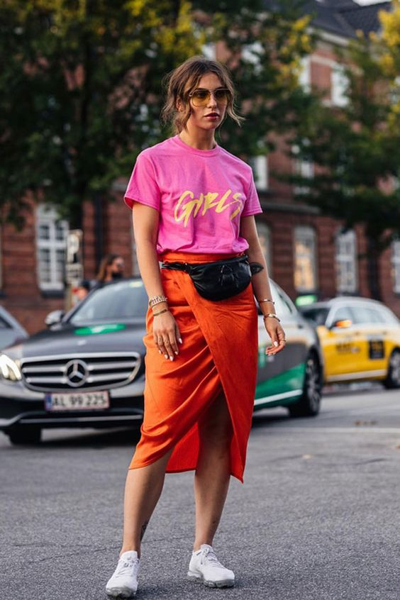 a hot red printed tee, an orange wrap midi skirt, white sneakers and a black waist bag