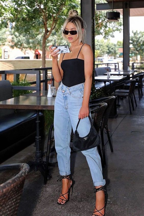 a hot summer outfit with a black spaghetti strap top, high waisted blue jeans, black lace up shoes and a baguette bag