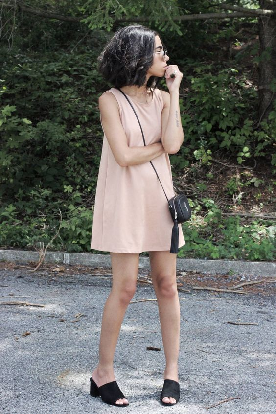 a minimalist pink mini dress with no sleeves, black heeled mules and a crossbody bag for spring and summer