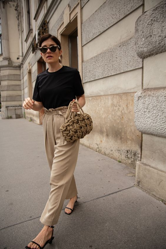 a minimalist work look with a black tee, tan pants with a high waist, black square toe sandals and a woven bag