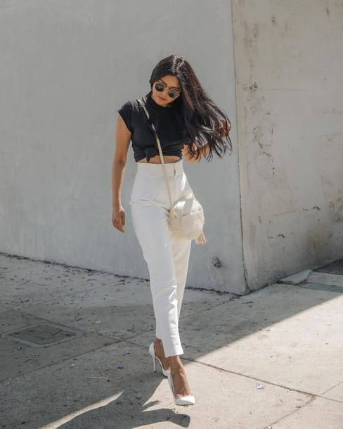 a monochromatic look with a black tie up tee, white high waisted pants, white pointed toe shoes and a round bag