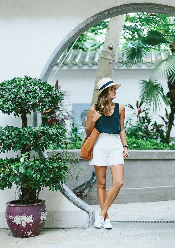 a monochromatic look with a black top, white mini shorts, white sneakers and a hat plus a brown tote