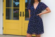 a navy polka dot knee dress, hot pink earrings and mules with block heels and tassels for a colorful touch