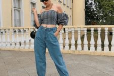 a party look with a plaid off the shoulder top, blue baggy jeans, red heels and a round black bag