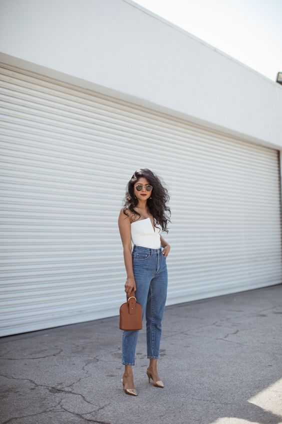 a party look with a white strapless top with a deep neckline, blue cropped jeans, metallic pointed toe shoes and a brown bag
