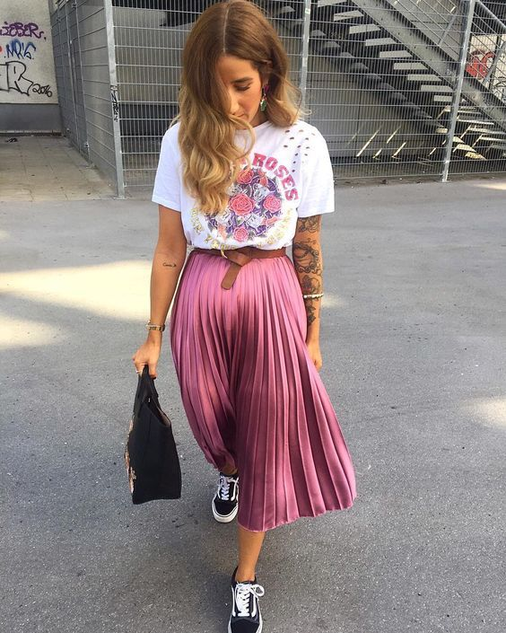 a printed t-shirt, a pink pleated midi skirt, black sneakers and a black bag for a girlish touch