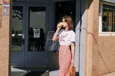 a printed t-shirt, a red knee printed skirt with buttons, tan strappy heels and a cognac bag