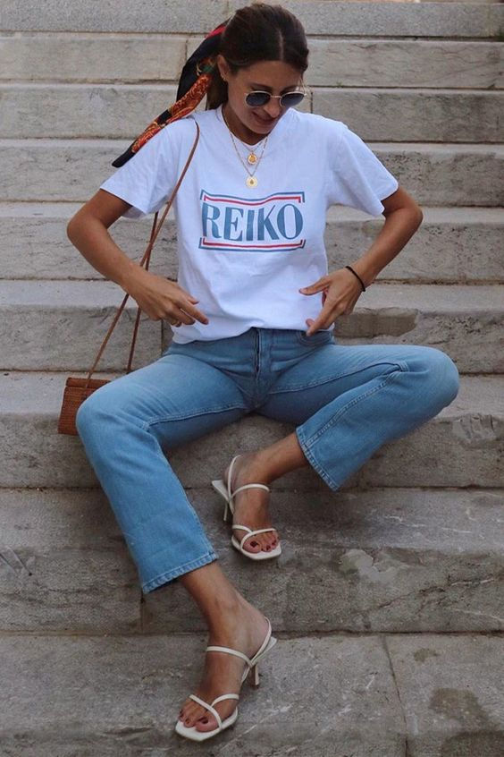 a printed tee, blue cropped jeans, white square toe sandals, a brown bag and layered necklaces