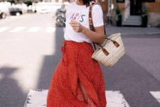 a printed white tee, a red printed midi skirt with a slit, burgundy lace up heels and a wicker bag