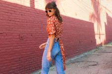 a red floral top with a sash, blue jeans, neutral heeled mules for a 90s inspired look