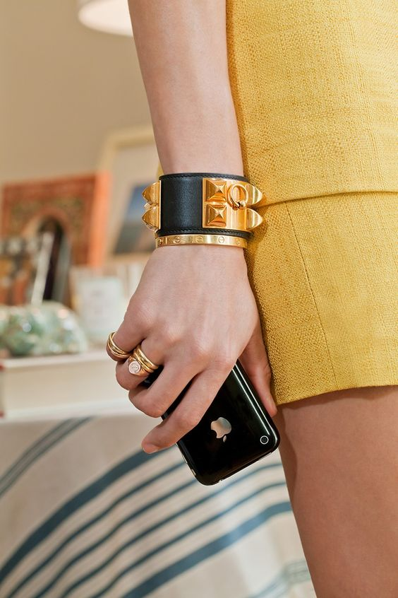 a refined statement bracelet of black leather and with gold touches plus stacked gold rings for a bold look