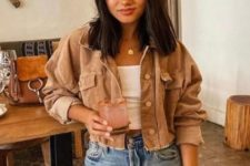 a relaxed look with a white crop top, blue ripped jeans, a tan cropped denim jacket for summer