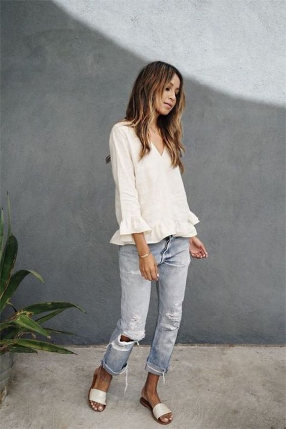 a relaxed summer look with a white linen top with ruffled sleeves, blue ripped jeans and white slippers