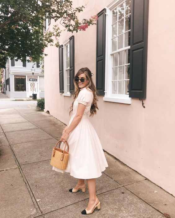 a romantic vintage-inspired white midi dress with short sleeves, two tone slingbacks and a wicker bag