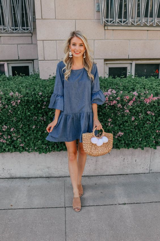 a ruffle denim dress, statement earrings, nude peep toe mules and a wicker bag