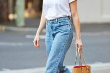 a simple everyday outfit with a white tee, blue baggy jeans, white sneakers and an amber tote