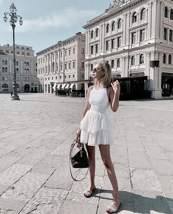 a simple look for a hot day with a white tank top, a layered white mini, boho slippers and a brown bag