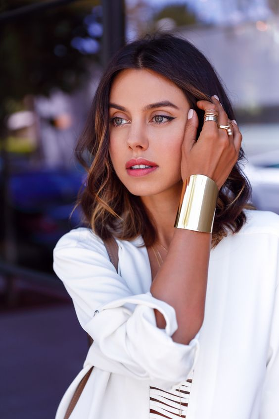 a statement gold bracelet and stacked gold rings including pearl ones for a chic and bold look