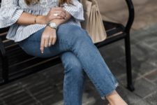 a striped blouse with appliques and ruffle sleeves, blue jeans, tan shoes and a neutral bag