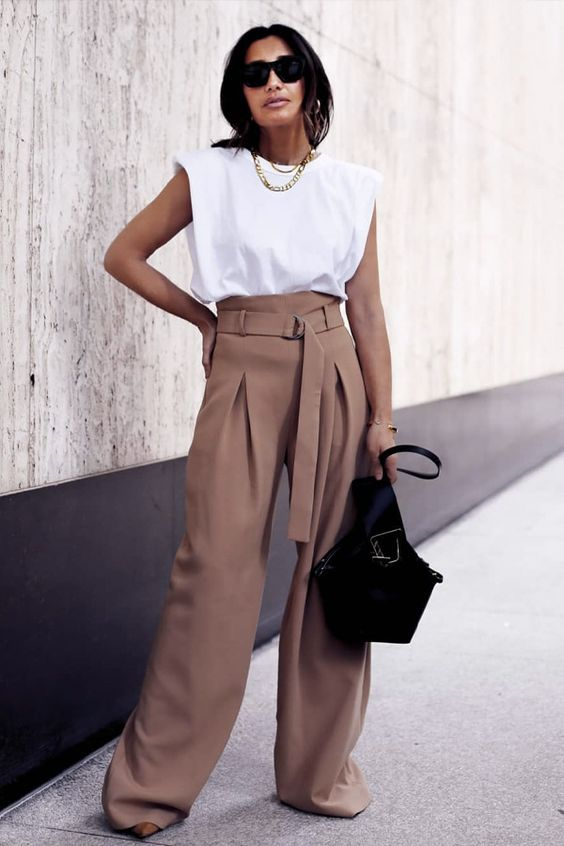 a stylish and trendy work look with a white padded shoulder tee, taupe high waisted palazzo pants, a black bag