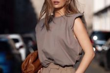 a stylish look with a taupe padded shoulder tee, matching pants and a brown bag plus geometric glasses