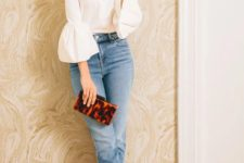 a stylish outfit with a white blouse with ruffle sleeves, blue jeans, twon tone slingbacks and a bright clutch