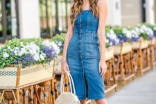 a summer look with a button front denim knee dress, nude block heels and a white wicker bag