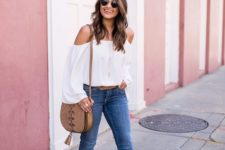 a summer outfit with a white off the shoulder blouse, blue skinnies, tan block heels and a saddle bag