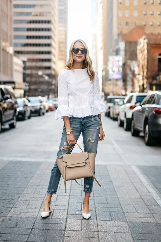 a summer outfit with a white top with ruffle sleeves, blue jeans, white shoes and a neutral bag