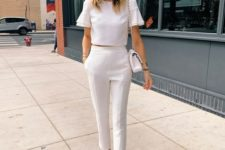 a summer work look with a white crop top with ruffle sleeves, white pants, tan shoes and a white bag