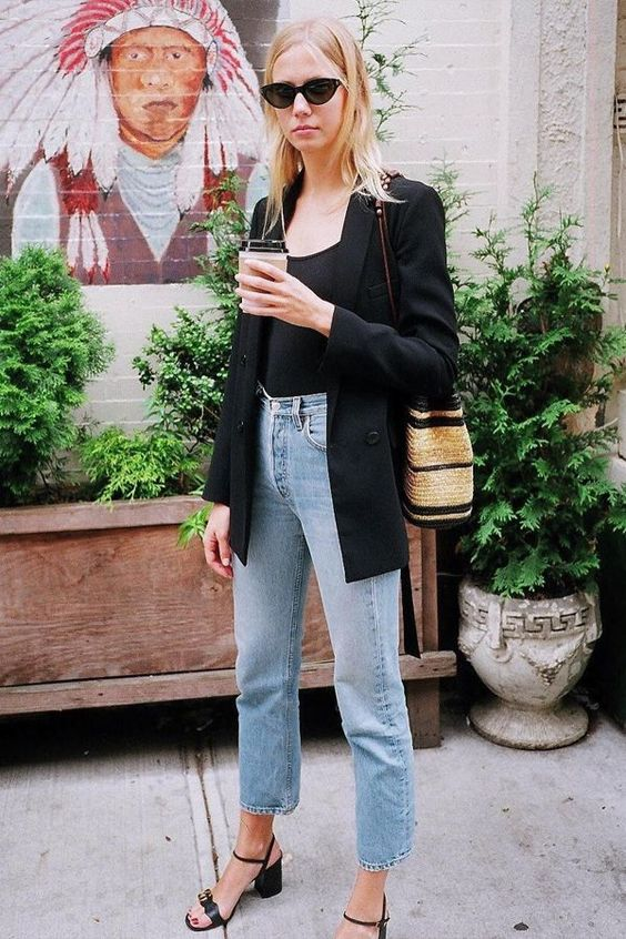 a summer work outfit with a black top, blue cropped jeans, a black blazer, black block heels and a woven bag