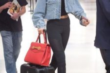 a travel outfit with a black crop top, joggers, a cropped denim jacket and white trainers by Gigi Hadid