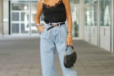 a trendy look with a black lingerie top, blue baggy jeans, black padded mules and a black saddle bag