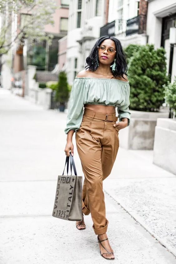 a trendy look with a green off the shoulder top, high waisted brown pants, black square toe sandals and a large tote