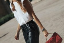 a trendy look with a white padded shoulder top, black reptile leather pants, square toe shoes and a red bag