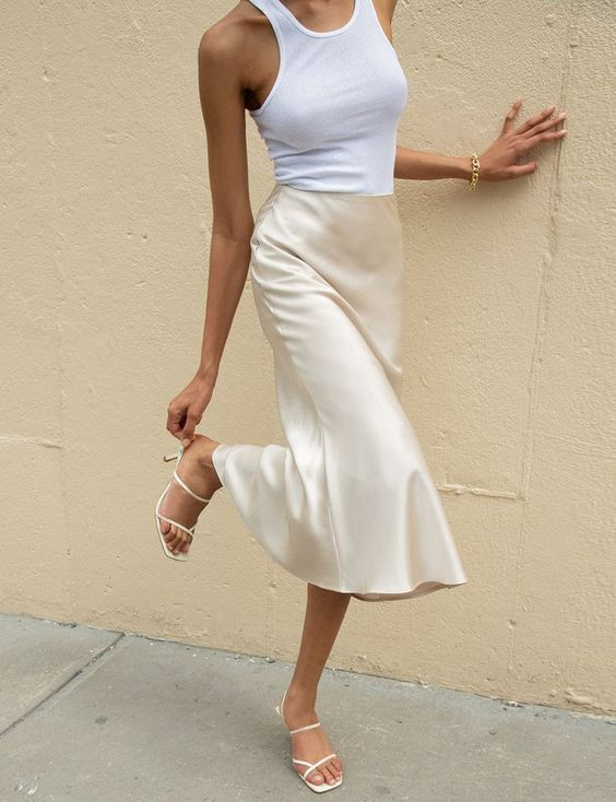 a trendy look with a white tank top, neutral satin midi, neutral strappy sandals for summer