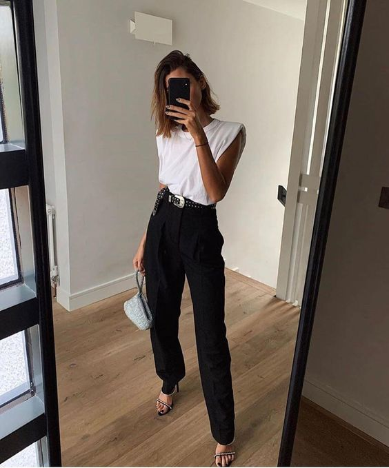 a trendy minimalist look with a white padded shoulder top, black pants, embellished shoes and a small bag