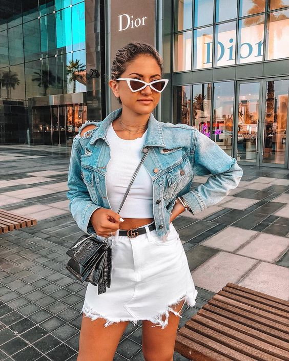 a trendy summer look with a white crop top, a white denim mini skirt, a blue cropped denim jacket and a crossbody