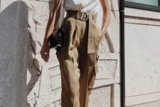 a trendy summer look with a white halter neckline top, tan high waisted pants, black strappy heels and a black bag